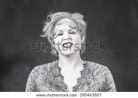 A woman making a crazy facial expression while shaking powder out of her hair. Her mouth open. Powder exploding everywhere.
