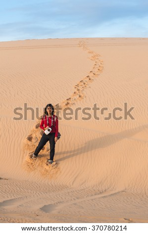 A woman making her footprints on desert in Vietnam. As she enjoy her travel.