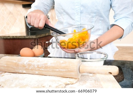 A woman mixes the peach filling for a pie she is baking.