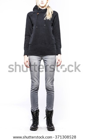 A woman(model, girl, female) stand up wearing black shirts with hood, blue denim(jeans, pants, trousers), black leather military boots isolated white at the studio.