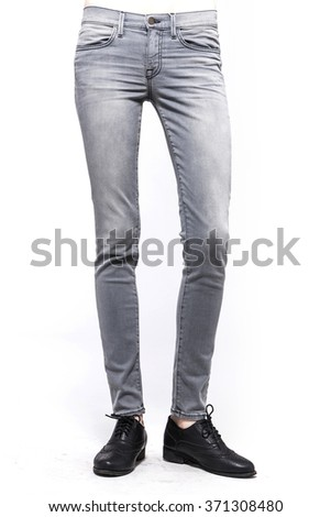 A woman(model, girl, female) stand up wearing grey denim(jeans, pants, trousers), black leather shoes isolated white at the studio.