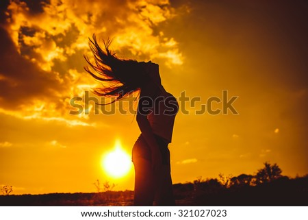 a woman of European appearance twenty years in the mountains sunset silhouette
