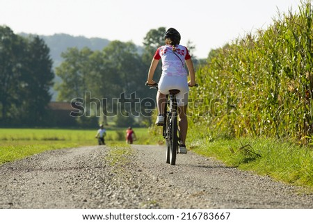 A woman on a cycle catching up with her friends in front.