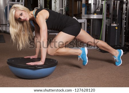 A woman on a half of a ball in plank position bringing in her knee. - stock photo