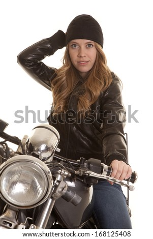 a woman on a motorcycle in her leather jacket and hat