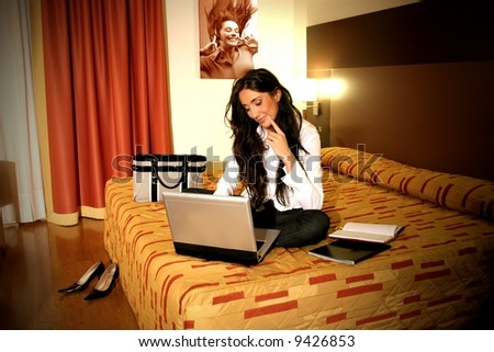 a woman on the bed with notebook in a room hotel - stock photo