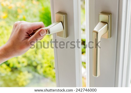 a woman opens a window to air the apartment. fresh air in the room - stock photo