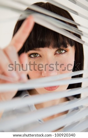 A woman opens her blinds to look through the window into the camera - stock photo
