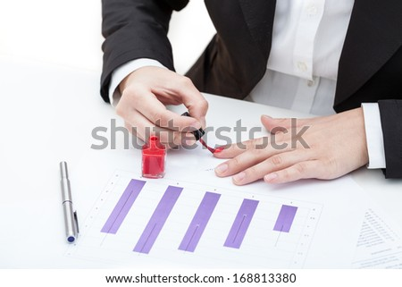 A woman painting her nails red at work