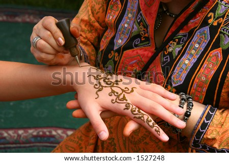 A woman paints a design on a girl with henna.