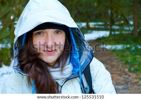 A woman pauses during her hike for a rest and to look at the camera while wearing a white jacket.