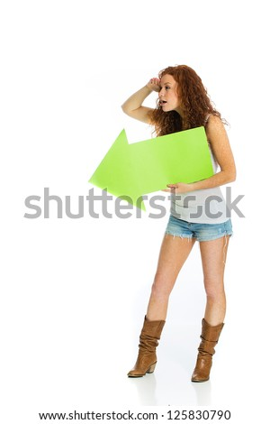 A woman peering off into the distance holding a green arrow pointing left. - stock photo