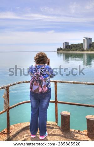 A woman photographs the sea, the beach and the promenade Cape Pitsunda - stock photo
