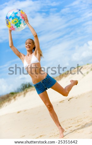 A woman playing a ball game on the beach