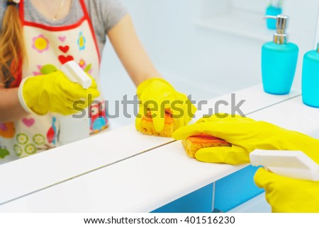 A woman polishing glass using a cleaning sponge and rubber gloves cleaning a mirror with a spray cleaner - stock photo