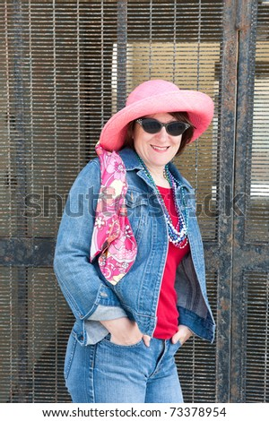 A woman poses against a metal security gate while wearing a colorful pink hat, vibrant scarf and sunglasses.