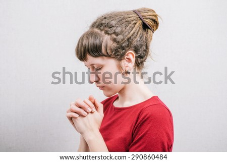 A woman prays and asks. Profile of a gray background.
