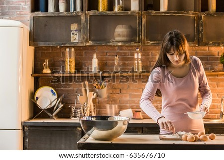 A woman prepares food in the kitchen and reads cooking recipes in the book. On the kitchen table lie the flour, eggs