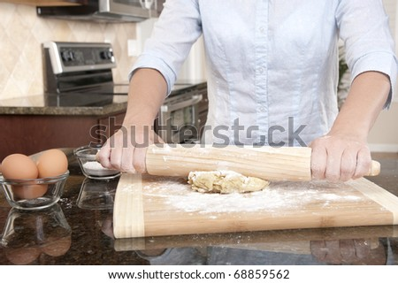A woman prepares some dough for baking food. - stock photo