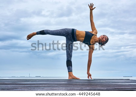 A woman professional trainer yoga pose on wooden bridge over seaside.