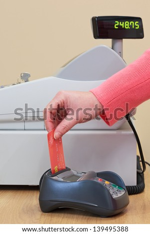 A woman putting her credit card into the card machine in a shop. - stock photo