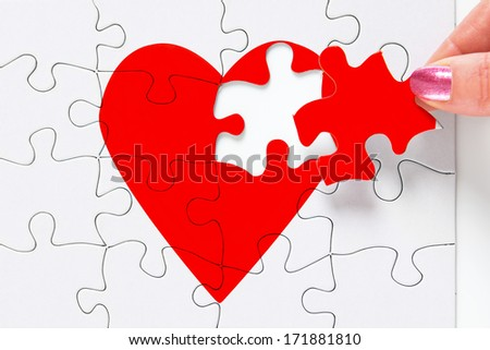 A woman putting the missing piece of a jigsaw red heart in place, good image to represent a love, broken heart, heartbreak, romance or Valentines theme. - stock photo