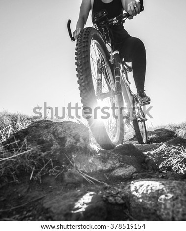a woman racing a bicycle down a dirt trail with big rocks in the back country to get away from the city toned with a retro vintage instagram filter app or action effect - cycling sport  - stock photo
