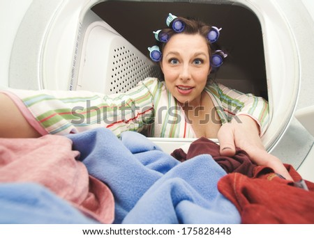 a woman reaching in the dryer for clothes - stock photo