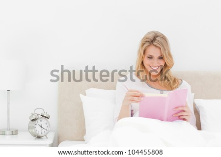 A woman reading a book and smiling as she sits in bed. The alarm clock on the desk beside her.
