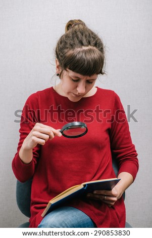 A woman reading a book with a magnifying glass. On a gray background.
