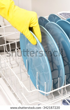 A woman removes dishes after they are finished being washed in a dishwasher - stock photo