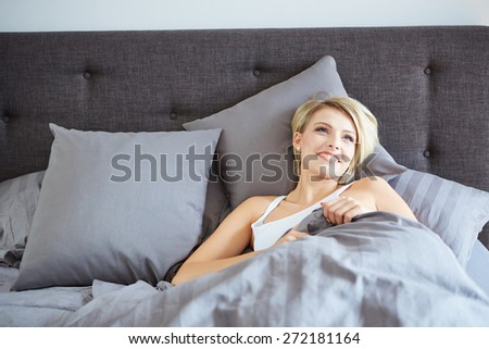 A woman resting in bed with hands beside her head on the pillow. - stock photo
