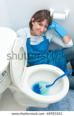 A woman rests with no motivation to clean the toilet in her home. - stock photo