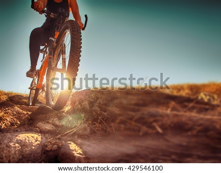 a woman riding a bicycle down a dirt trail with big rocks in the back country to get away from the city toned with a retro vintage instagram filter app or action effect