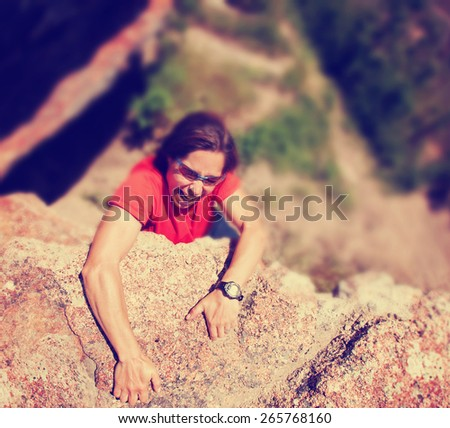 a woman rock climbing on a cliff during summer toned with a soft vintage instagram like filter  - stock photo