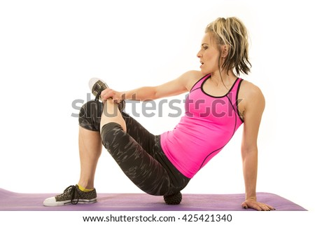 A woman rolling out her body on a massage ball, after a workout. - stock photo