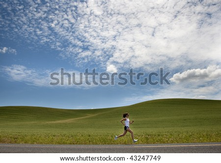A woman running down a road with green hills and blue sky in the distance - stock photo