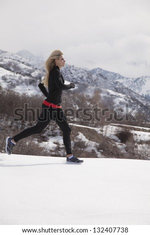 A woman running in the snow out in the outdoors.