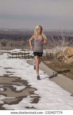 A woman running in the snow trying to be healthy and fit. - stock photo