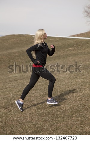 a woman running up a hill where there is still snow.