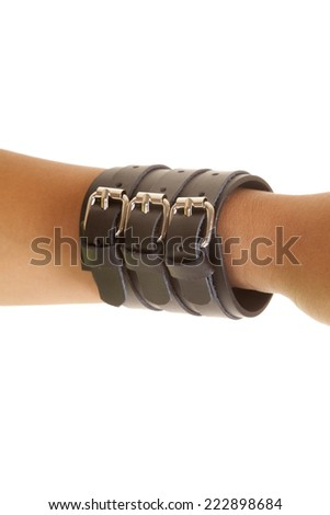 A woman's arm on a white background with a leather buckle bracelet.