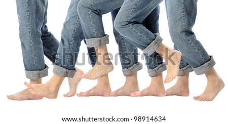 A woman's bare feet advance one step forward in rolled up jeans on white - stock photo