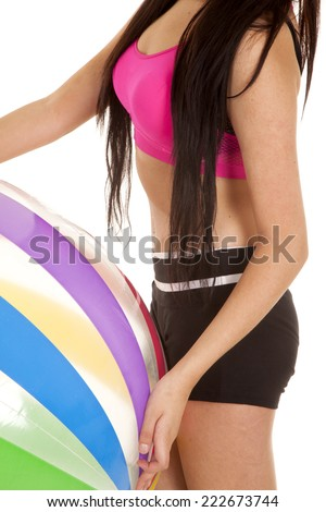 A woman's body holding on to a beachball. - stock photo