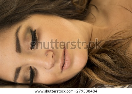 A woman's face up close, with a tattoo showing through her hair. - stock photo