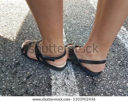 a woman's feet wearing dark sandals on asphalt