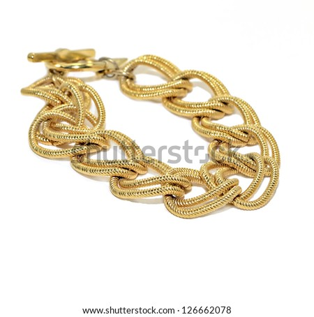 A woman's gold chain bracelet on white. - stock photo