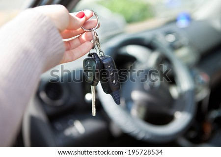A woman's hand gives the keys to the car - stock photo