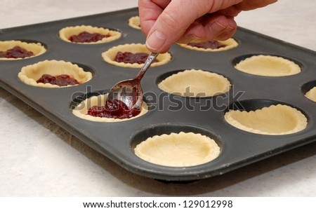 A woman's hand holding a teaspoon as she fills jam tarts with raspberry conserve - stock photo