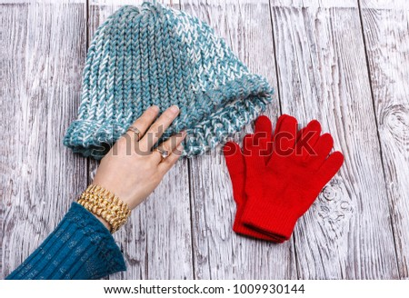 A woman's hand is reaching for the wool knit hat y the red gloves.