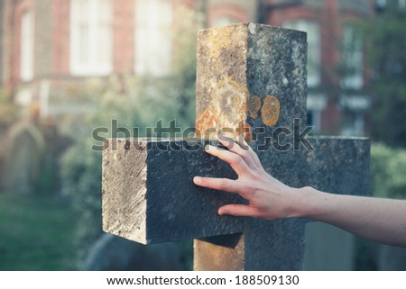 A woman's hand is touching a gravestone at sunset - stock photo